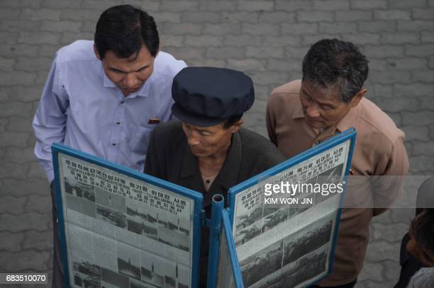 TOPSHOT In a photo taken on May 15 2017 people gather at a streetside newsstand showing a copy of the Rodong Sinmun newspaper featuring coverage of a...