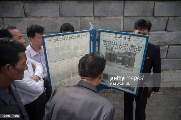 In a photo taken on May 15 2017 people gather at a streetside newsstand showing a copy of the Rodong Sinmun newspaper featuring coverage of a May 14...