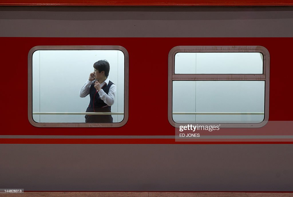 In a photo taken on May 19, 2012 a stewardess talks on a mobile phone as she stands in the window of a train carriage at a station in Beijing. A slew of bleak data has raised fears China's economy is cooling faster than previously thought, but analysts say Beijing has only limited means to prevent a politically damaging slowdown. AFP PHOTO / Ed Jones
