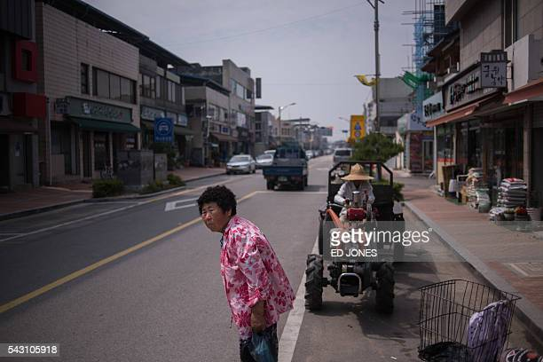 In a photo taken on May 27 2016 an elderly woman waits to cross a road in Gunwi some 200 kilometres south of Seoul By 2030 a quarter of all South...