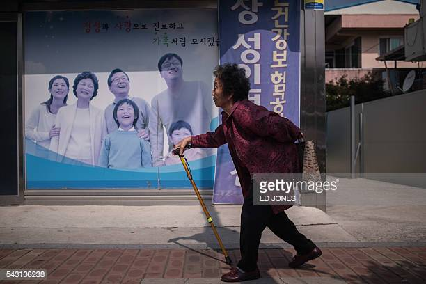 In a photo taken on May 27 2016 an elderly woman walks past a poster at a health centre in Gunwi some 200 kilometres south of Seoul By 2030 a quarter...
