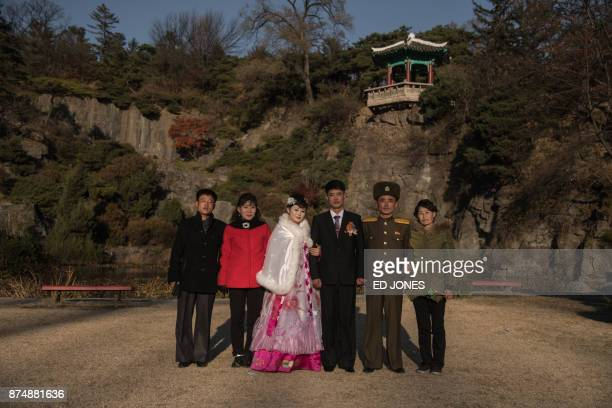 In a photo taken on November 15 a bride and groom pose for pictures in a park in Pyongyang / AFP PHOTO / Ed JONES
