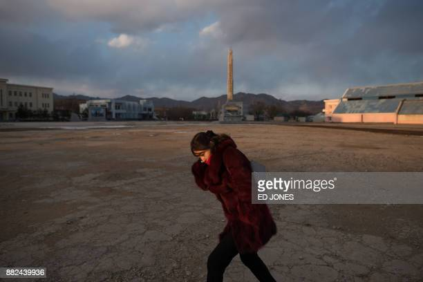 In a photo taken on November 21 a woman shields herself from the cold at the port in Rason At the northeastern tip of North Korea where the isolated...