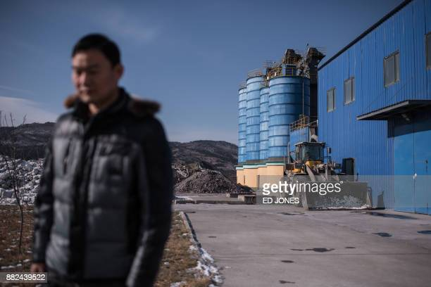 In a photo taken on November 21 Han Yue deputy manager of the Chineseowned Rason Songsin Building Materials cement plant stands outside a processing...