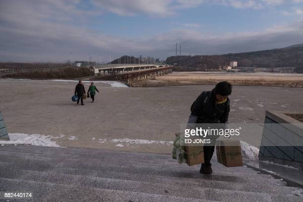 In a photo taken on November 21 people arrive on the North Korean side of the border between North Korea and China and the entrance to the Rason...