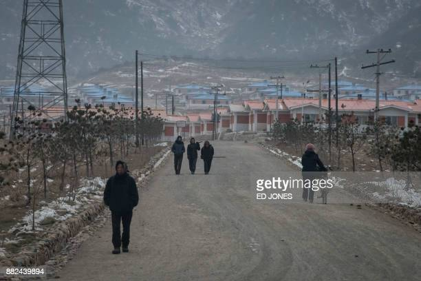 In a photo taken on November 21 people make their way along a road near Rason At the northeastern tip of North Korea where the isolated nucleararmed...