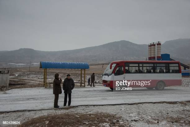 In a photo taken on November 21 people stand at the side of a road near the city of Rason At the northeastern tip of North Korea where the isolated...