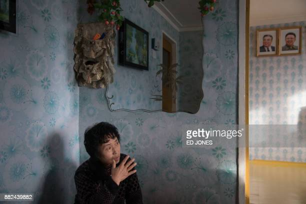 TOPSHOT In a photo taken on November 21 Ra InHae sits in her new home after her old house was damaged by flooding before the portraits of late North...