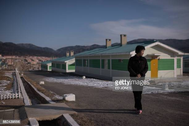 In a photo taken on November 21 Ra InHae stands outside her new home in a development for people who lost their old homes to flooding near the city...