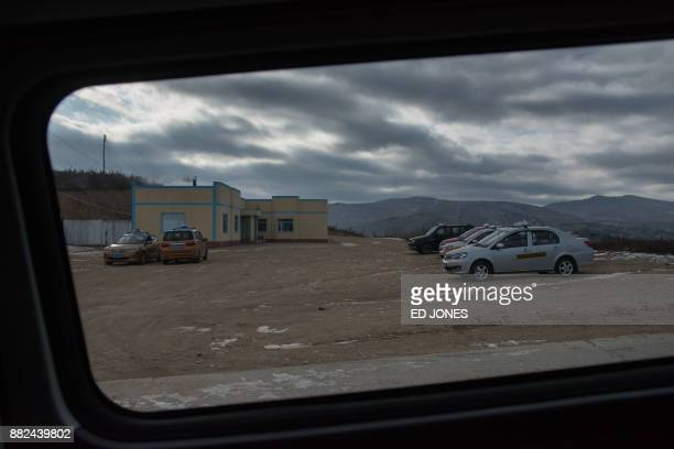 In a photo taken on November 21 taxis wait at a parking area near the North Korean boder with China to collect business people crossing into the...