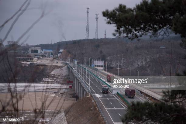 In a photo taken on November 21 vehicles make their way across a bridge across the Tumen river marking the border between North Korea and China and...