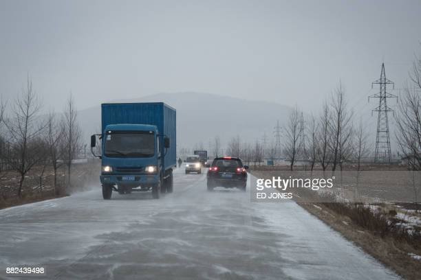 In a photo taken on November 21 vehicles make their way along a road linking the Chinese border crossing with the Rason Special Economic Zone At the...