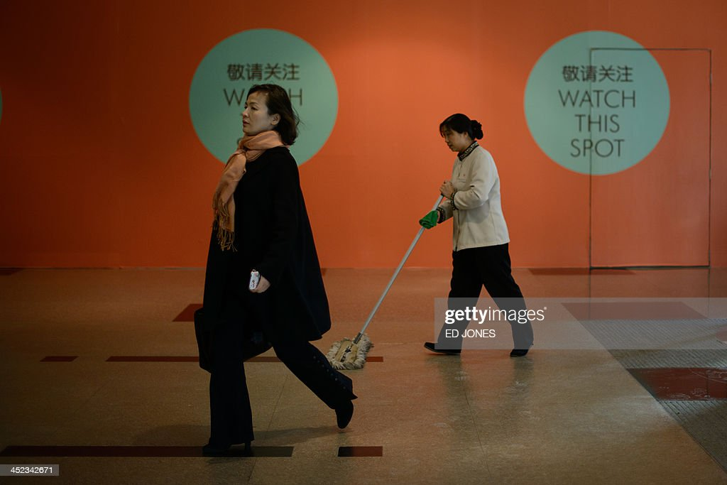In a photo taken on November 27, 2013 a woman walks past a janitor inside a shopping mall in Beijing. China's new free-trade zone has drawn just 38 overseas firms in its first two months of operations, officials said, as foreign companies await concrete policies and deeper reforms. AFP PHOTO / Ed Jones