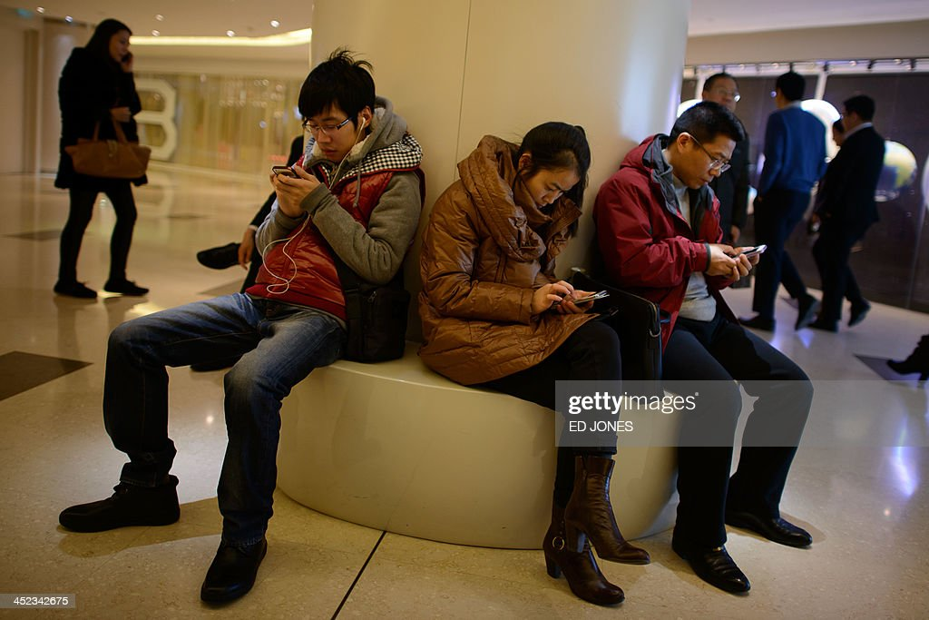 In a photo taken on November 27, 2013 people use their mobile phones as they sit inside a shopping mall in Beijing. China's new free-trade zone has drawn just 38 overseas firms in its first two months of operations, officials said, as foreign companies await concrete policies and deeper reforms. AFP PHOTO / Ed Jones