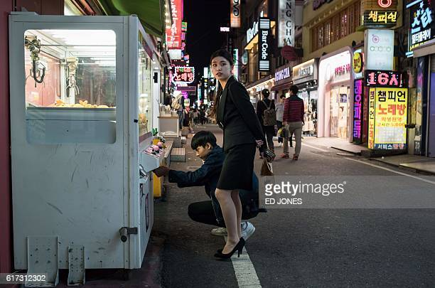 In a photo taken on October 20 2016 a couple play a streetside game in the central South Korean city of Daejeon / AFP / Ed Jones