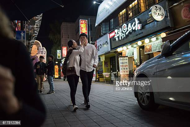 In a photo taken on October 22 2016 a couple walk along a street in the central South Korean city of Daejeon / AFP / Ed Jones
