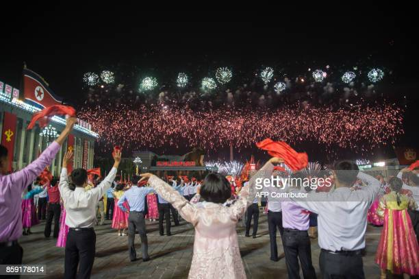 TOPSHOT In a photo taken on October 8 2017 participants described as 'working people youth and students of Pyongyang' watch fireworks as they perform...