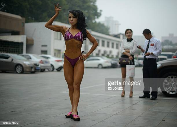 In a photo taken on September 15 an amateur 'body fitness' competitor from China practices her moves before competing in a bodybuilding contest in...