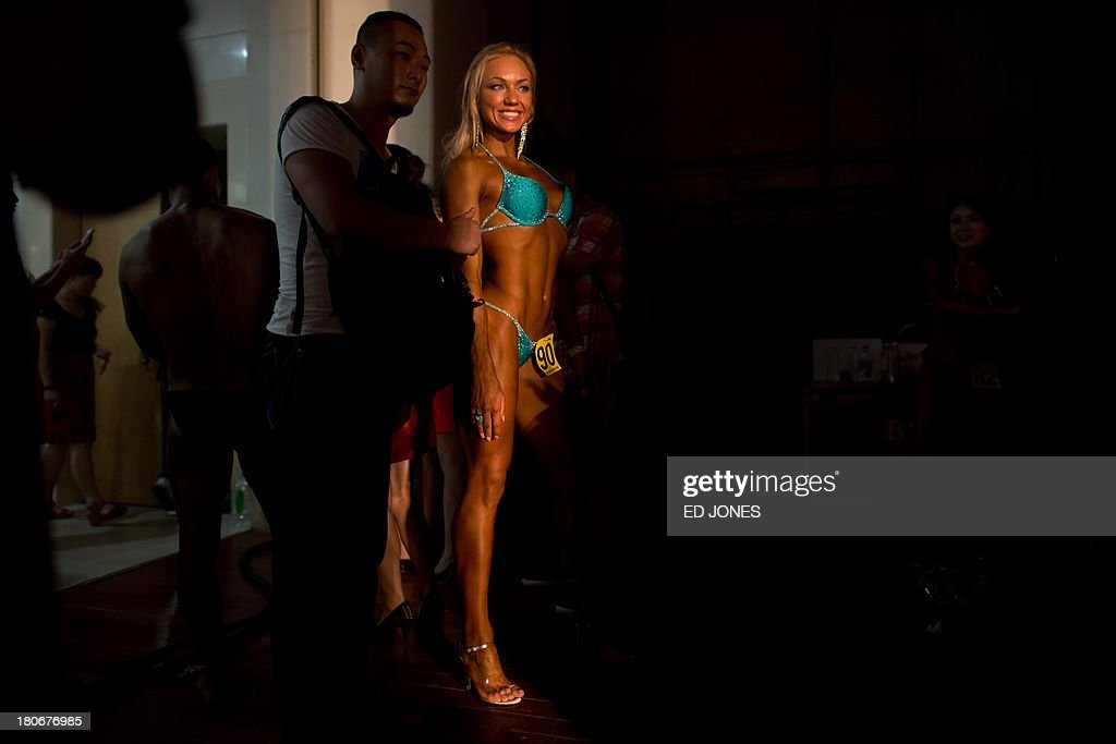 In a photo taken on September 15, 2013, 'bikini fitness' competitor Svetlana Borushko of Russia (C) waits backstage before taking part in a bodybuilding contest in Zhengzhou, Henan province. More than 20 professionals -- including a dozen from China -- were competing in the Bodybuilding Grand Prix in the central Chinese city for a top prize worth 80,000 yuan (13,000 USD). They were joined by scores of amateurs from across the country, in what event organisers said was a sign of the increasing popularity of muscle building in China. Bodybuilding has at least a century of history in China, but fell out of favor following the Communist revolution in 1949, when competitions were sometimes banned and the sport condemned as western and bourgeois. But it has since enjoyed a resurgence and competitors say the growing number of competitions are boosting the ranks of local professionals. AFP PHOTO / Ed Jones