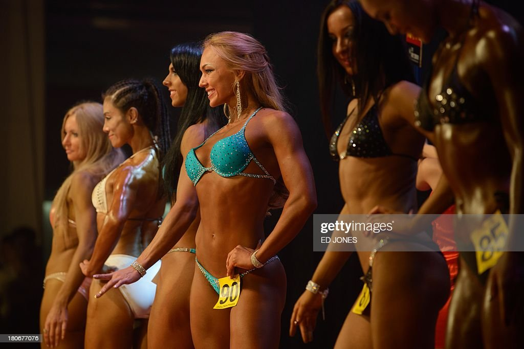 In a photo taken on September 15, 2013, 'bikini fitness' competitors pose on stage during a bodybuilding contest in Zhengzhou, Henan province. More than 20 professionals -- including a dozen from China -- were competing in the Bodybuilding Grand Prix in the central Chinese city for a top prize worth 80,000 yuan (13,000 USD). They were joined by scores of amateurs from across the country, in what event organisers said was a sign of the increasing popularity of muscle building in China. Bodybuilding has at least a century of history in China, but fell out of favor following the Communist revolution in 1949, when competitions were sometimes banned and the sport condemned as western and bourgeois. But it has since enjoyed a resurgence and competitors say the growing number of competitions are boosting the ranks of local professionals. AFP PHOTO / Ed Jones