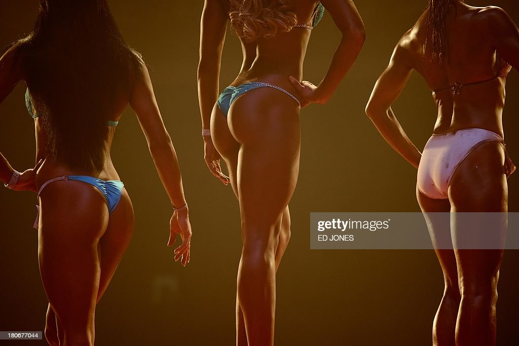 In a photo taken on September 15, 2013, 'bikini fitness' competitors stand on the podium during a bodybuilding contest in Zhengzhou, Henan province. More than 20 professionals -- including a dozen from China -- were competing in the Bodybuilding Grand Prix in the central Chinese city for a top prize worth 80,000 yuan (13,000 USD). They were joined by scores of amateurs from across the country, in what event organisers said was a sign of the increasing popularity of muscle building in China. Bodybuilding has at least a century of history in China, but fell out of favor following the Communist revolution in 1949, when competitions were sometimes banned and the sport condemned as western and bourgeois. But it has since enjoyed a resurgence and competitors say the growing number of competitions are boosting the ranks of local professionals. AFP PHOTO / Ed Jones