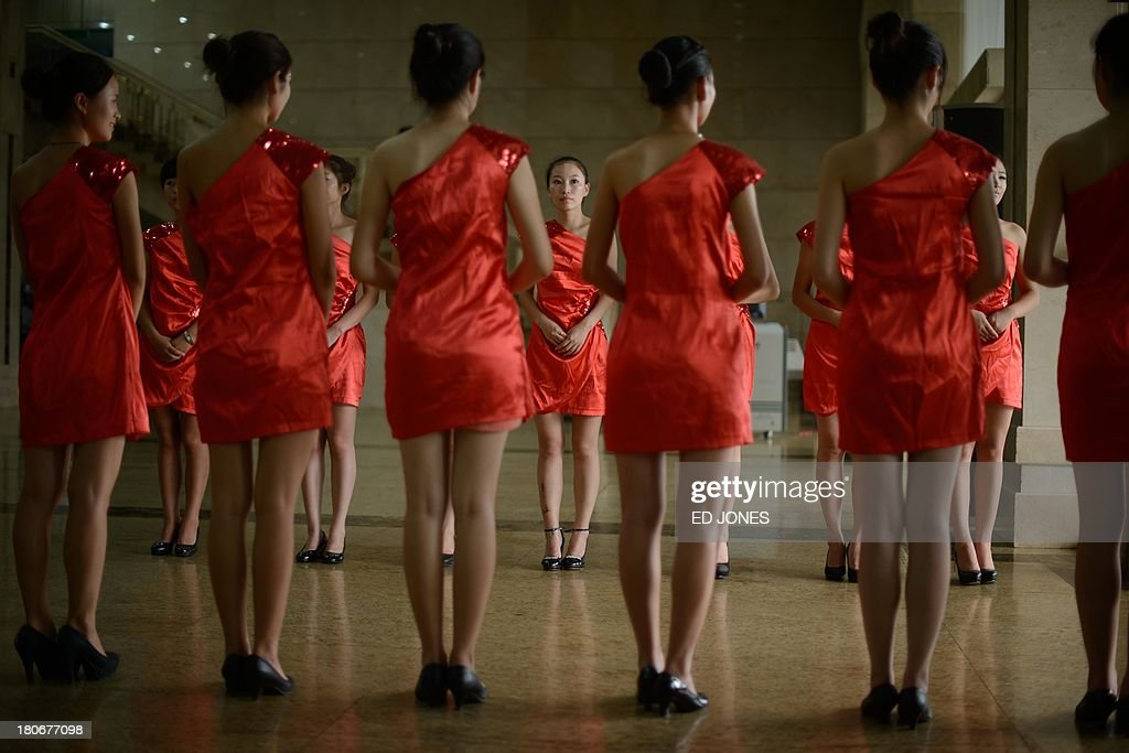 In a photo taken on September 15 hostesses wait to greet spectators prior to a bodybuilding contest in Zhengzhou Henan province More than 20...