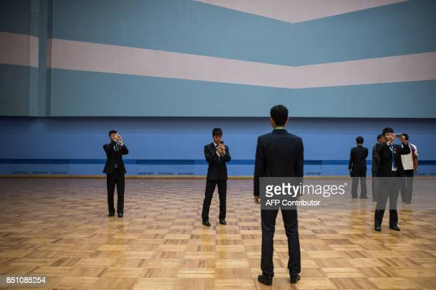 In a photo taken on September 21 2017 North Korean staff members take photos during the 20th ITF World Taekwondo Championships in Pyongyang The world...