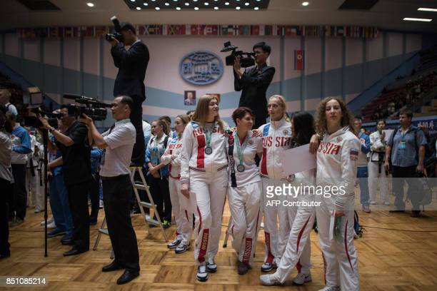 In a photo taken on September 21 2017 team members from Russia cheer theoir compatriots during the medal ceremony of mens team event during the 20th...
