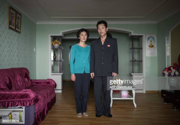 In a photo taken on September 26 2017 husband and wife Ri Jae Gyong and Kim Yu Gyong pose for a portrait in their highrise apartment at Ryomyong...