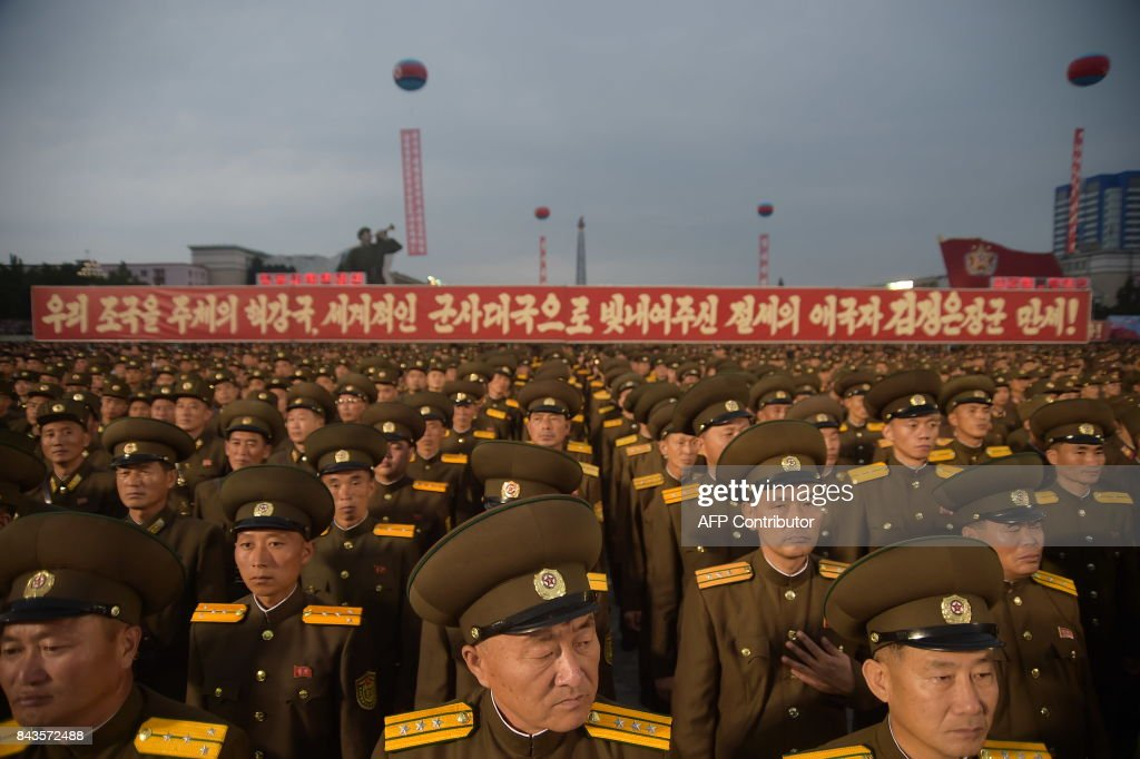 TOPSHOT - In a photo taken on September 6, 2017, Korean People's Army (KPA) soldiers attend a mass celebration in Pyongyang for scientists involved in carrying out North Korea's largest nuclear blast to date. Citizens of the capital lined the streets September 6 to wave pink and purple pom-poms and cheer a convoy of buses carrying the specialists into the city, and toss confetti over them as they walked into Kim Il-Sung Square. / AFP PHOTO / Kim Won-Jin