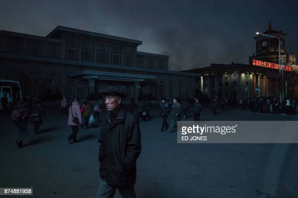 In a photo taken through the window of a car pedestrians illuminated by a public television screen walk past the central station in Pyongyang on...