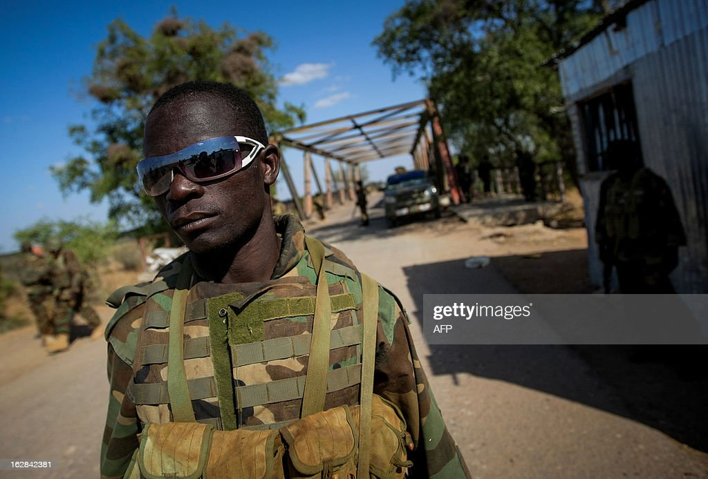 CREDIT 'AFP PHOTO / AU-UN IST PHOTO / STUART PRICE' - NO MARKETING NO ADVERTISING CAMPAIGNS - DISTRIBUTED AS A SERVICE TO CLIENTS In a photograph taken and released by the African Union-United Nations Information Support team on February 28, 2012, a Ugandan soldier serving with the African Union Mission in Somalia (AMISOM) stands in front of a bridge approx. 7km east of the central Somali town of Buur-Hakba following it's capture the day before from the Al-Qaeda-affiliated extremist group Al Shabaab by the Somali National Army (SNA), supported by AMISOM forces. The strategically important town linking the capital Mogadishu and the hinterlands of central Somalia was liberated without a shot being fired, marking a significant loss for the group. The town, located 64kms east of Baidoa, Somalia's second city, was a stronghold of the Shabaab where they extorted high levies of illegal taxation on the local civilian populations and used it as a base from where they planned and launched attacks against government forces and installations, AMISOM and the Somali population.