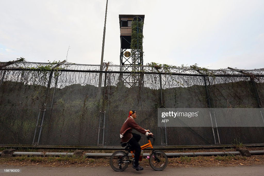 In a picture taken on December 26, 2012, a man rides a bicycle near an abandoned watchtower at a wire fence in Hong Kong near the border with the neighbouring southern Chinese city of Shenzhen. A plan to allow millions more mainland Chinese to visit Hong Kong was delayed in August as the southern city said it needed to consult with Beijing over its ability to cope with the influx.