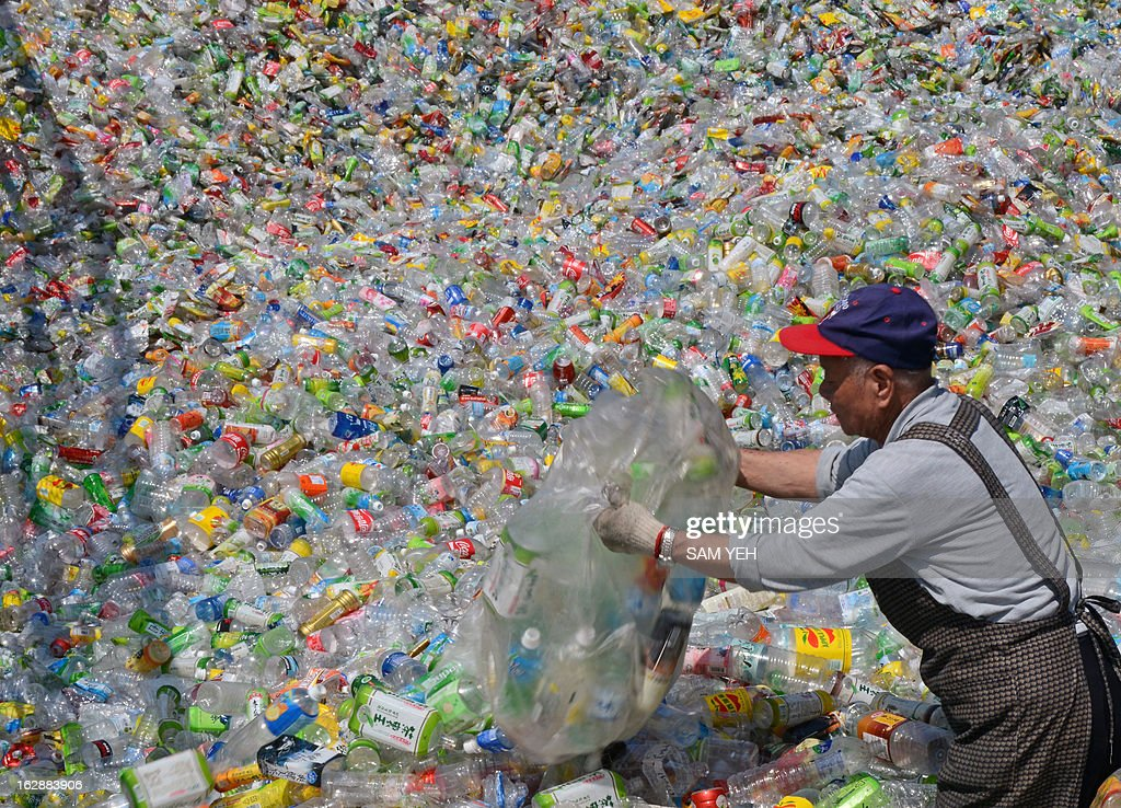 In a picture taken on February 28, 2013, a volunteer of the Taiwan Buddhist Tzu Chi Foundation sorts through plastic bottles at a recycling plant in Taipei. Some 40 people stand ankle-deep in used plastic bottles in the yard of a recycling station in Taipei, stamping them flat in the first step of a process that will transform the junk into usable goods. AFP / Sam YEH
