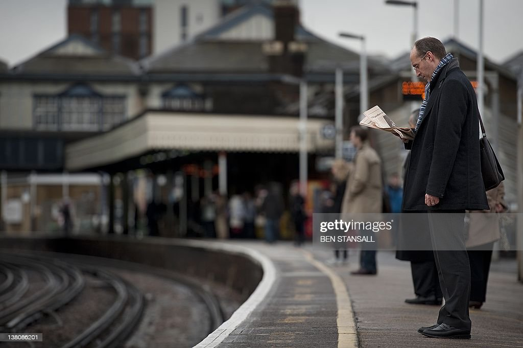 In a picture taken on January 19 2012 rail passengers wait for a train on the platform at Clapham Junction train station in south London Delays in...