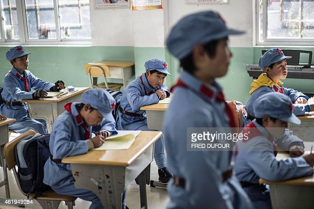 In a picture taken on January 21 children dressed in uniform attend class at the Beichuan Red army elementary school in Beichuan southwest China's...