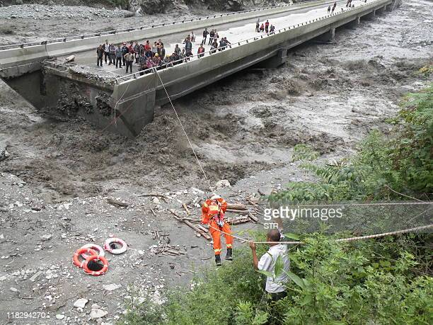 In a picture taken on July 4 2011 a firefighter uses a rope to rescue a group of 36 Chinese villagers stranded on a section of road which was...