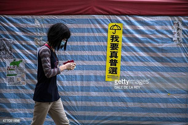 In a picture taken on June 13 a woman walks past an 'umbrella movement' sticker on a tent erected by prodemocracy protesters along a sidewalk outside...