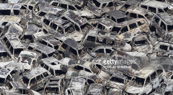 In a picture taken on March 12 2011 burnt out vehicles that were parked for export are piled in disarray at a port at Tokai village in Ibaraki...