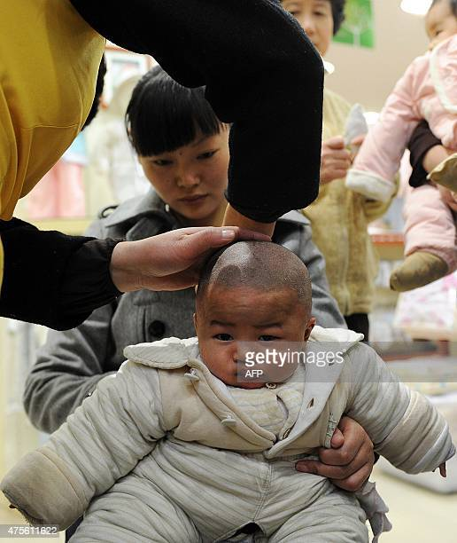 In a picture taken on March 17 2010 a barber gives a young child a haircut at a barbershop in Hefei in Anhui province on the second day of the second...