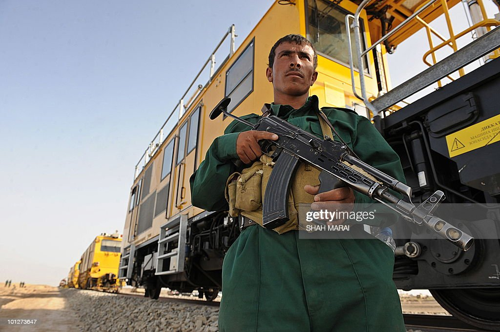 In a picture taken on May 25, 2010 an Afghan policeman stands guard near a new railway track inaugurated in Hairatan. In the harsh desert heat on the northern border with Uzbekistan, workers are hammering down the tracks of Afghanistan's first railway which Afghanistan says is a revolutionary project that could revive the poverty-stricken, war-ravaged, landlocked country's status as a thriving 'silk road' trade hub. AFP PHOTO/SHAH Marai