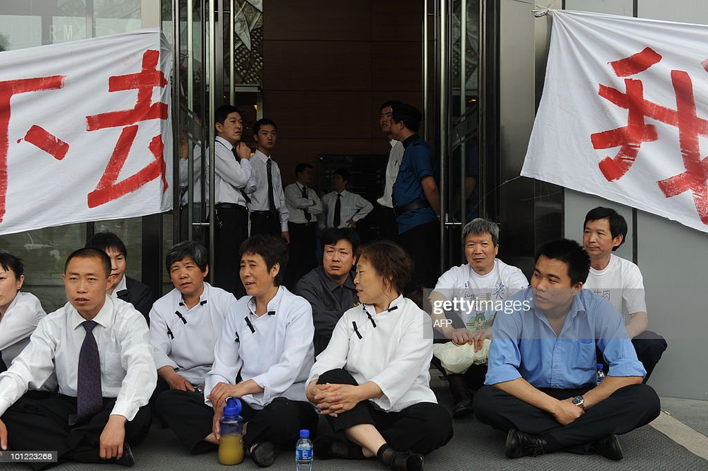 In a picture taken on May 27, 2010 contract labourers sit in front of banners saying 'We need to survive' as they protest during a labour dispute outside an office in Beijing. China issued new rules making it harder to fire workers recently, in a sign Beijing is seriously concerned about the rising unemployment. CHINA