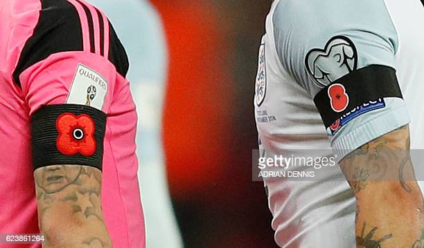 In a picture taken on November 11 2016 Poppy armbands worn by England's defender Kyle Walker and Scotland's forward Leigh Griffiths to comemorate...