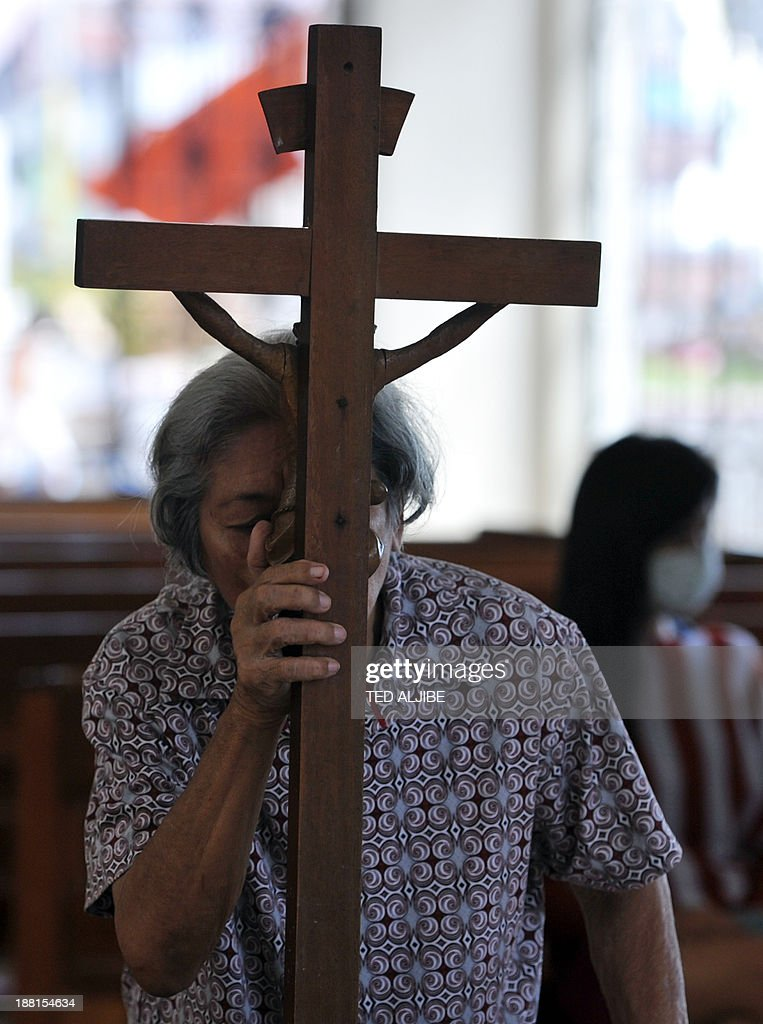 In a picture taken on November 15, 2013, a resident kisses a crucifix as she prays at the destroyed Santo Nino church (child Jesus) in Tacloban city, Leyte province, central Philippines. Santo Nino church stands battered but tall in the ruins of its typhoon-shattered parish, a 124-year-old beacon of physical and spiritual sanctuary for a devout, traumatised community.