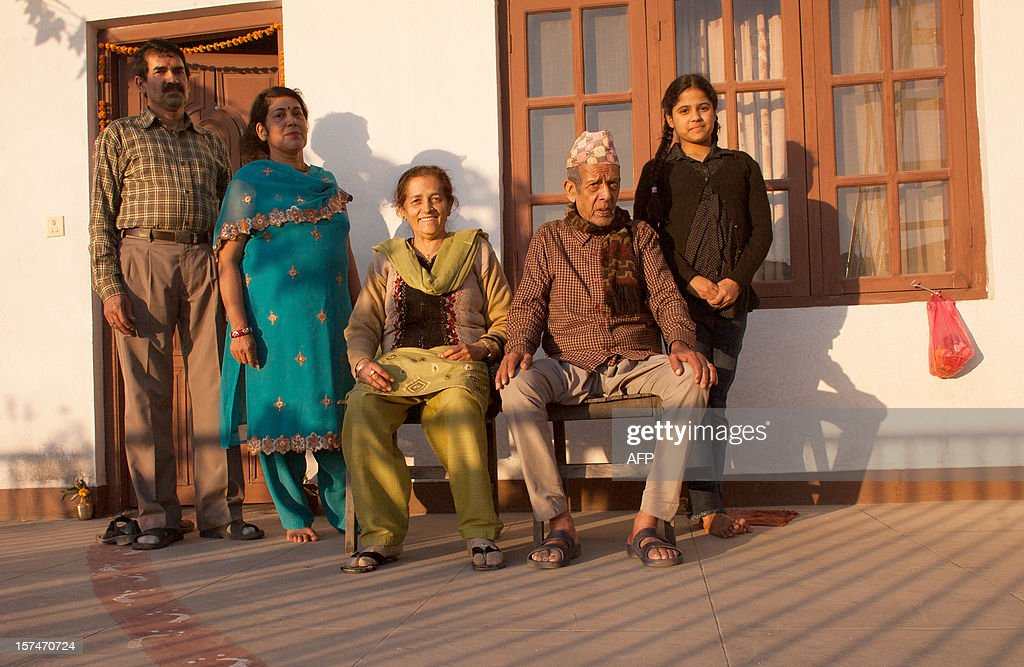 In a picture taken on November 21, 2012, Drishti Silwal (R), a 12 year old Brahmin Nepali girl poses with (L-R) her uncle, her aunt, her grandmother and grandfather, who took care of her since birth as her mother refused to care for her, at their home in Kathmandu. Dristhi returned to school after spending 7 days staying in the darkness of her bedroom as part of an isolation ritual during her first menstruation. Usually Brahmans stay isolated for 21 days in the dark, without the permission to look outside, see any men, pray or cook, but in modern families the ritual can be reduced to 7 days and Drishti was allowed to read. AFP PHOTO / MATTHIEU ALEXANDRE