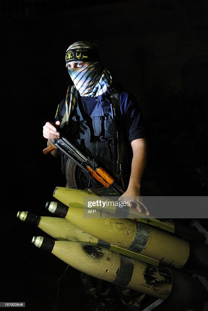 In a picture taken on November 25, 2012, a Palestinian militant from the armed wing of the Islamic Jihad organization displays rockets at an undisclosed location in the Hamas-run Gaza Strip. During the eight-day confrontation earlier this month with Israel, Hamas and Islamic Jihad still managed to fire five rockets at the Tel Aviv area, three of which were intercepted by the Iron Dome defence system, with another two landing in the Mediterranean Sea.