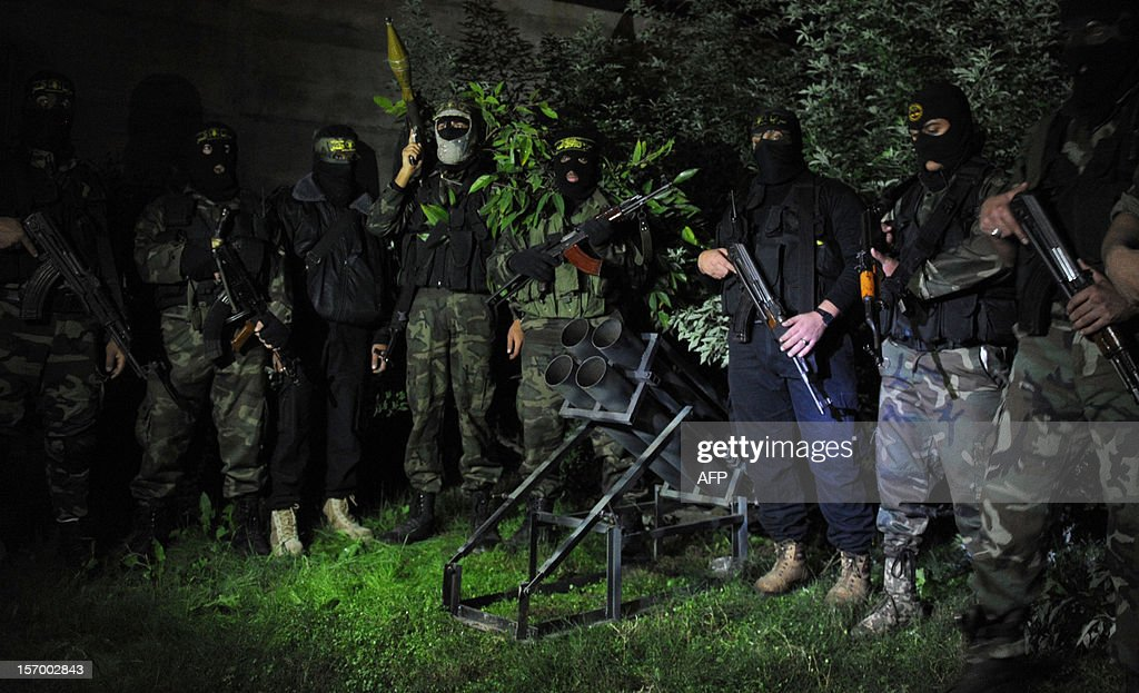 In a picture taken on November 25 Palestinian militants from the armed wing of the Islamic Jihad organization stand around a rocket launcher at an...