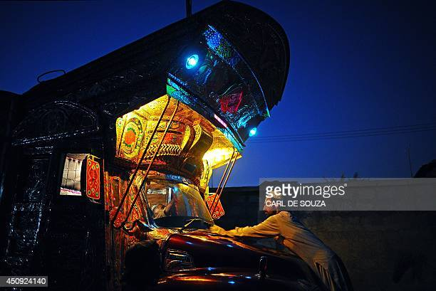 FORUM In a picture taken on October 4 2010 a truck painter buffs the bodywork of a truck at night at master painter Hussain Noor's workshop in...