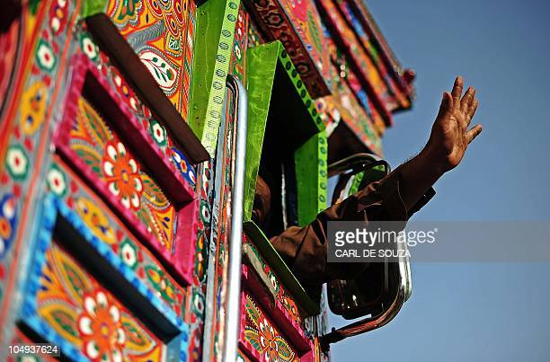 FORUM In a picture taken on October 6 2010 a truck driver waves goodbye as he drives the finished truck away from a workshop in Peshawar Colourful...