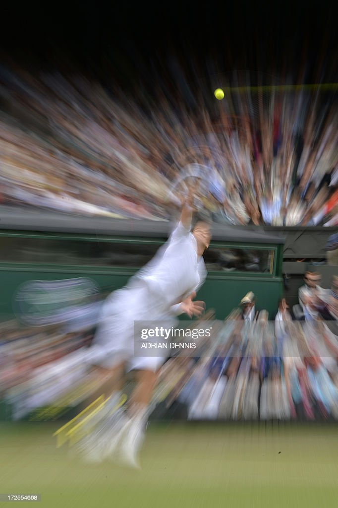In a picture taken with a slow shutter speed and a zoom burst effect Britain's Andy Murray serves against Spain's Fernando Verdasco during their men's singles quarter-final match on day nine of the 2013 Wimbledon Championships tennis tournament at the All England Club in Wimbledon, southwest London, on July 3, 2013.